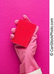hand in protective glove holding red sponge over purple...