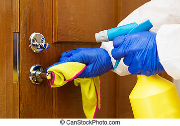 Hand in protective glove with rag cleaning door handle. Covid-19 disinfection concept.