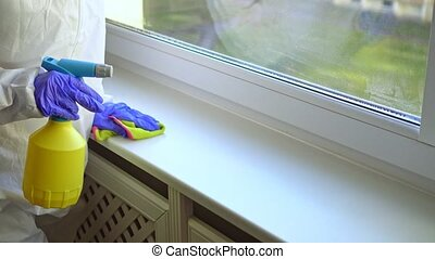 Hand in protective glove with rag cleaning windowsill. Covid...