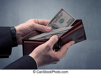 Hand in suit takes out dollar from wallet