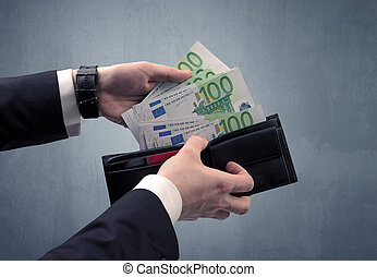Hand in suit takes out euro from wallet
