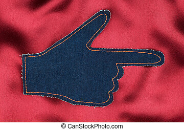Hand in the shape a pointer made of denim jeans on red satin