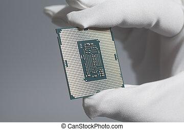 Hand in white glove holding a CPU computer processor microchip
