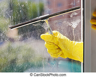 hand in yellow glove cleans window by squeegee - hand in...