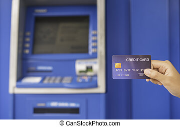 Hand inserting with a credit card into bank machine . Man using an atm machine with credit card to withdraw money