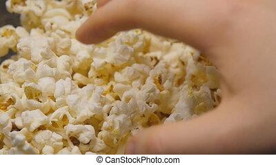 Hand is grabbing popcorn. - Popcorn. Hand is grabbing...