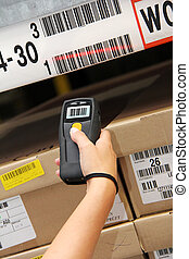 barcode scanner - hand is holding a handheld barcode scanner