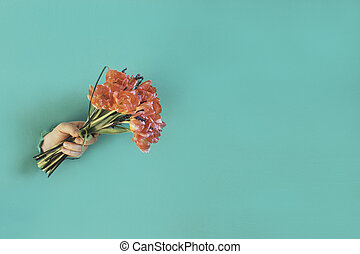 Hand is holding bouquet of flowers.