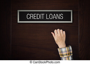 Female hand is knocking on Credit Loans bank department door looking for a service