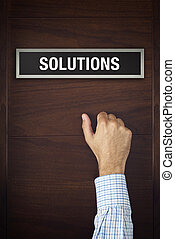 Male hand is knocking on Solutions bureau door, conceptual image.