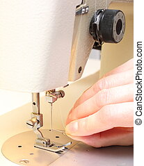 Hand is trying to thread the needle of a sewing machine