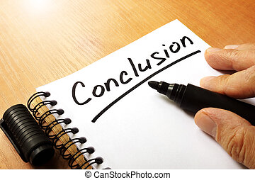 Hand is writing Conclusion on a note.