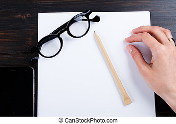 Hand is writing on a white list of paper with a pen composition. mock up design