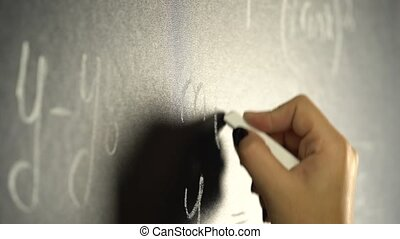 Hand is writing with a chalk a mathematical of a formula on...