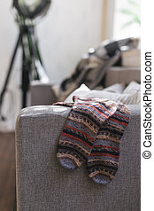 Hand knitted socks on the sofa in modern interior. Natural colors.