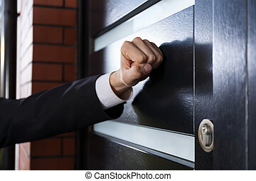 Hand knocking on the door - Close-up of hand knocking on the...