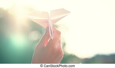 Hand launches paper airplane against sunset background. Slow...