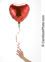 Hand Letting Go Of Heart Shaped Balloon