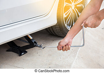 Hand lifting a car with spanner jack-screw