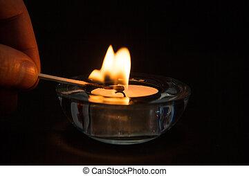 Hand lighting tea light candle in the dark