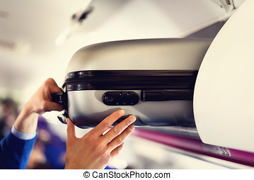 Hand-luggage compartment with suitcases in airplane. Hands take off hand luggage. Passenger put cabin bag cabin on the top shelf. Travel concept with copy space.