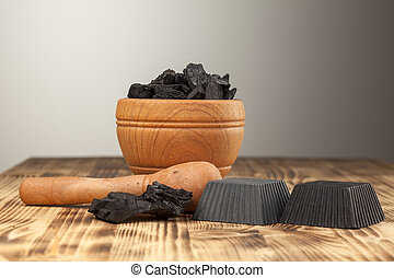 two hand made black soap from activated carbon on a wooden plank