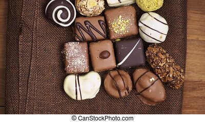 Hand made chocolate candies falling on wooden background, tasty sweets in slow motion