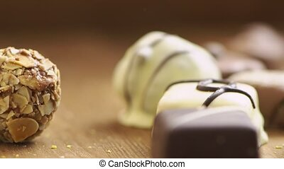 Hand made chocolate candies falling on wooden background, tasty sweets in slow motion uhd