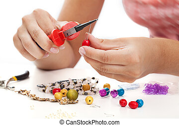 A person designing colorful earrings with plastic beads