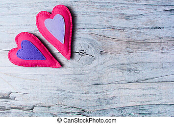 Hand made felt colorful hearts on wooden background