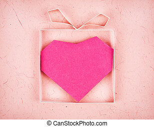 Hand made gift box with heart inside, textured paper as background. Greeting card