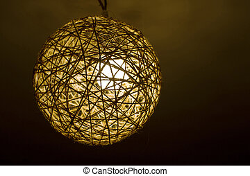 hand-made a lamp from ropes hangs on a ceiling