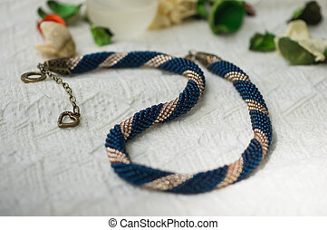 Hand-made necklace from beads of blue and gold color