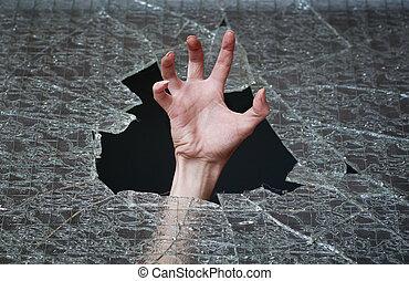 hand make their way through the broken glass
