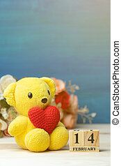 hand make yarn red heart put on yellow teddy bear beside wooden block calendar set on Valentines date 14 February in front of rose flower bouquet and blue background. Concept of valentines day.