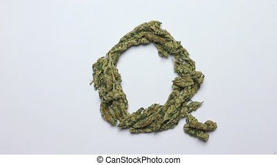 hand makes the letter Q of the English alphabet from cannabis