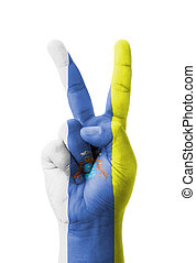 Hand making the V sign, Canary Islands flag painted