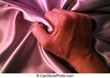 Hand - Man grabbing satin sheet on the bed.