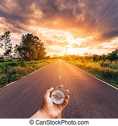 Hand man holding compass on road with sky sunset.