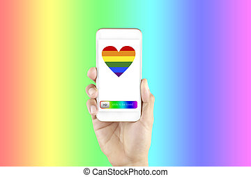 Hand man holding smart phone in screen show LGBT symbols. Hand hold phone with rainbow heart screen isolated on rainbow background with copy space. LGBT Concept freedom. Lesbian, gay, bisexual and transgender