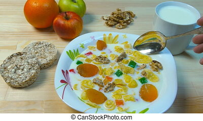 Hand mixing flakes in a bowl. Healthy breakfast