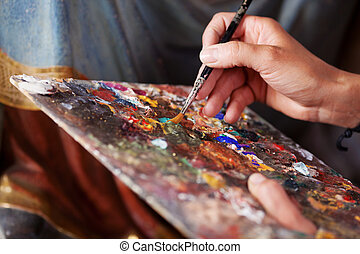 Hand Mixing Paint On Palette - Closeup of hand mixing paint...