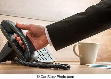 Hand of a businessman holding black landline telephone handset to pick it up