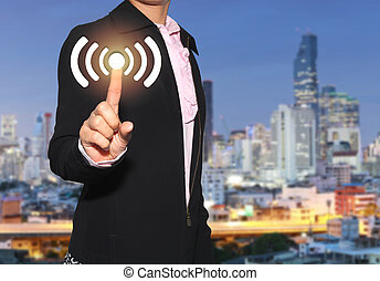 Hand of a businesswoman use finger to touch communication signal icon on skyscraper background.