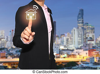 Hand of a businesswoman use finger to touch home and communication signals icon on skyscraper background.