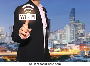 Hand of a businesswoman use finger to touch wifi icon on skyscraper background.