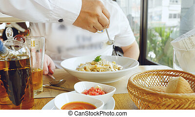 Hand of a chef puts the Parmesan over the pasta dish...