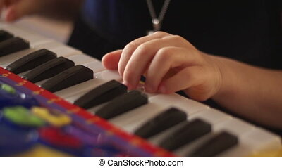 Hand of a child playing keys