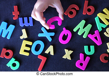 Hand of a little child learns the english language alphabet