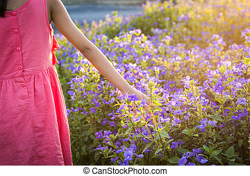Hand of a little girl touching wildflower in the meadow